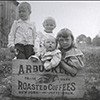 Four children sitting in an Arbuckles Roasted Coffee shipping case